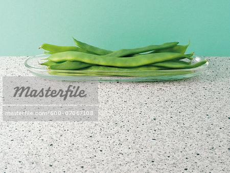 Raw, green, runner beans in glass dish on countertop, studio shot