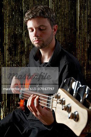 male musician playing bass guitar