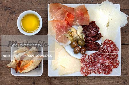 Antipasti: sundried tomatoes, olives, parmesan, Parma ham, olive oil, bread, salami, pickled artichokes