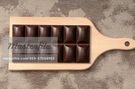 A bar of chocolate on a chopping board