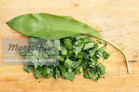 A wild garlic leaf and chopped wild garlic