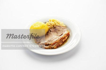 Roasted shoulder of pork with potato dumplings and sauerkraut