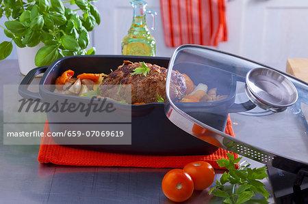 Roast ham with tomatoes, potatoes and garlic