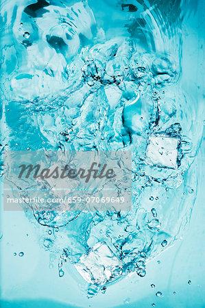 Ice Cubes Splashing into Water
