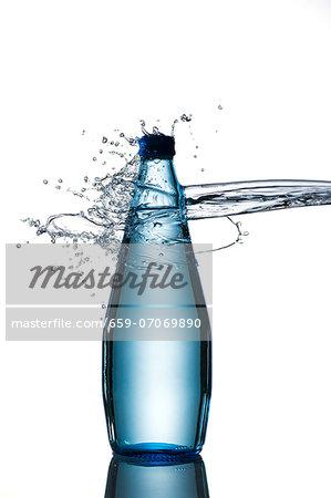 A splash hitting a bottle of water