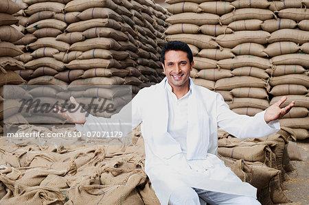 Man sitting on sack of wheat grains, Anaj Mandi, Sohna, Gurgaon, Haryana, India