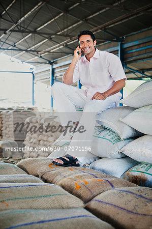 Man sitting on stack of wheat sacks and talking on a mobile phone in a warehouse, Anaj Mandi, Sohna, Gurgaon, Haryana, India