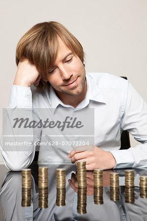 Smiling man at desk looking at stacks of coins