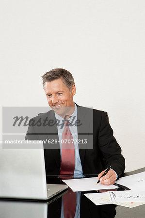 Smiling manager using laptop at desk
