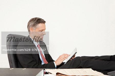 Smiling manager at desk using tablet computer