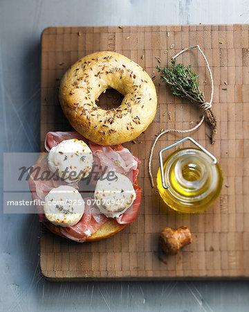 Raw ham and roast goat's cheese bagel sandwich