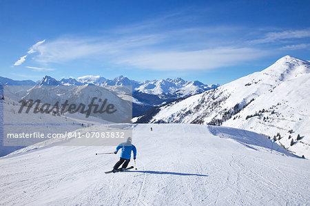Skiers on Levasset blue piste in winter sunshine, Champagny, La Plagne, French Alps, France, Europe