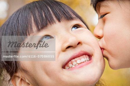 A girl kissing her older sister