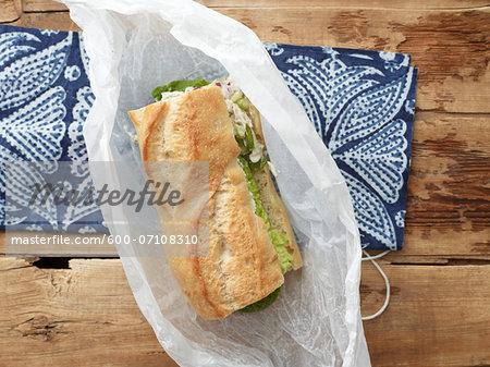 Overhead View of Chicken Salad Sandwich on Baguette in Wax Paper, Studio Shot