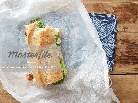 Overhead View of Chicken Salad Sandwich on Baguette with Bite Taken in Wax Paper, Studio Shot