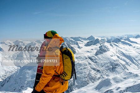 Back country skier taking a look at mountain range, European Alps, Tyrol, Austria