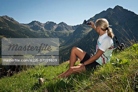 Female cyclist taking picture, mountain range in background, Kleinwalsertal,  Vorarlberg, Austria