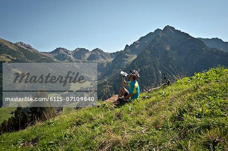 Mountain biker takes a rest, drinking water, Kleinwalsertal, Vorarlberg, Austria