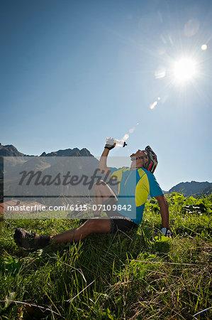 Mountain biker takes a rest drinking water, Kleinwalsertal, Vorarlberg, Austria