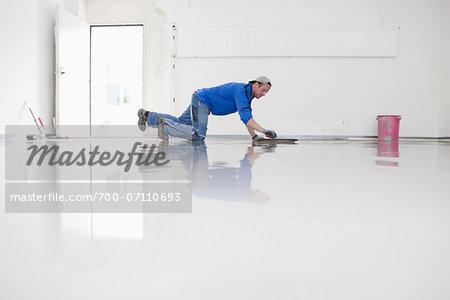 Tradesman Working on new Floor Cover in Garage, Mulheim, North Rhine-Westphalia, Germany