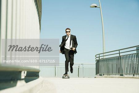 Businessman skateboarding on walkway holding binder, Germany