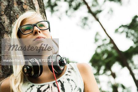 Portrait of girl wearing eyeglasses, standing next to tree in park, with headphones around neck, looking upward, Germany