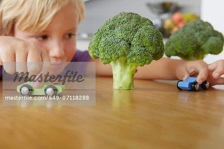 Boy playing cars around broccoli trees