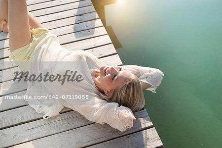 Young woman sunbathing on lake pier