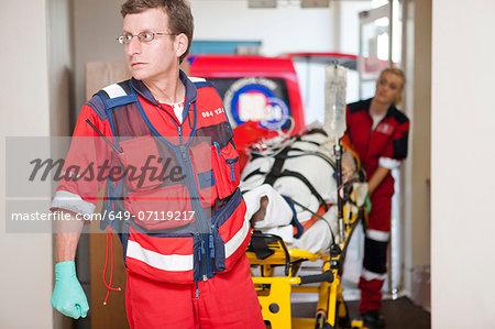 Paramedics wheeling stretcher through hospital