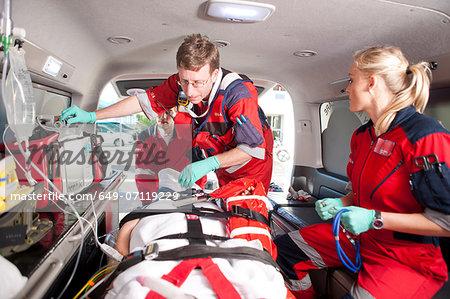 Paramedics checking patient in ambulance