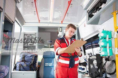 Paramedic in ambulance listing equipment