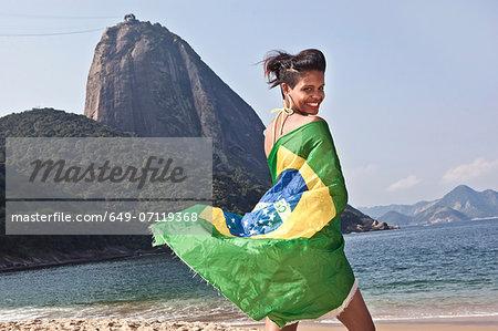 Man on beach with Brazilian flag, Rio de Janeiro, Brazil