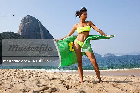 Man standing on beach with Brazilian flag, Rio de Janeiro, Brazil