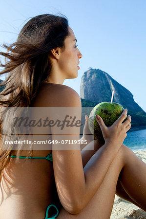 Young woman holding coconut drink, Rio de Janeiro, Brazil