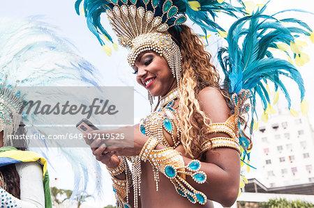Samba dancer using cellphone, Rio De Janeiro, Brazil