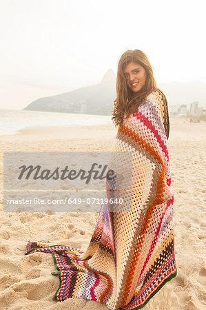 Young woman wrapped in blanket,  Ipanema Beach, Rio de Janeiro, Brazil