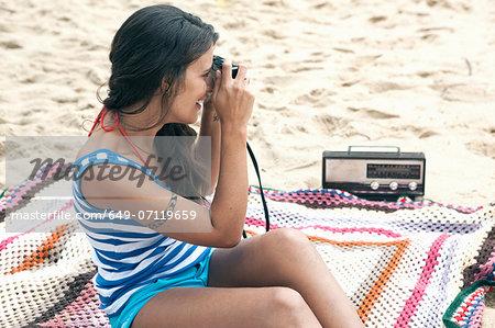 Woman on blanket on beach using camera