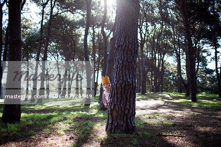Little boy in crown playing hide seek in forest