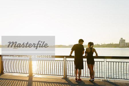 Jogging couple standing on riverside