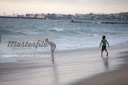 Two boys playing on Huntington Beach, California, USA