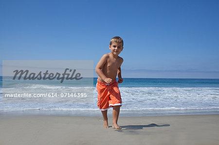 Young boy running on beach