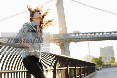 Young woman with windswept hair, Manhattan Bridge, Brooklyn, USA