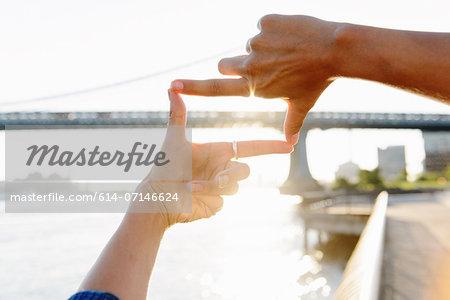 Woman's fingers framing Manhattan Bridge, Brooklyn, USA