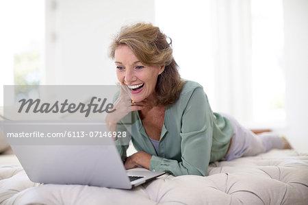 Senior woman using laptop in living room