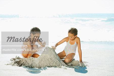 Girls building sandcastle on beach