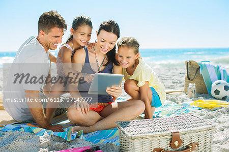 Family using digital tablet on beach
