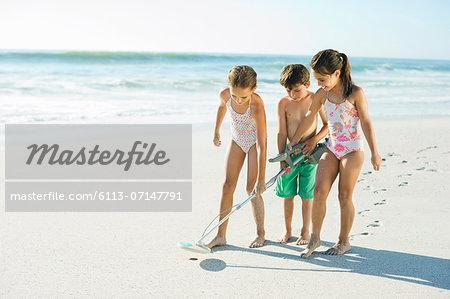 Children using metal detector on beach