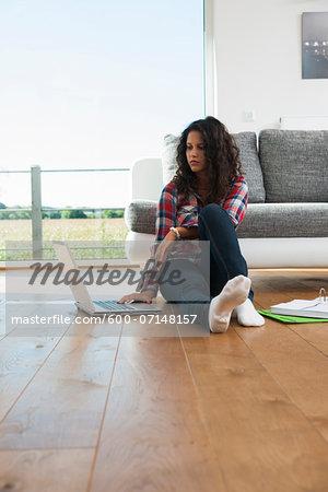 Teenage girl sitting on floor next to sofa, using laptop computer, Germany