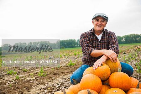 Farmer in field, next to pumpkin crop, Germany