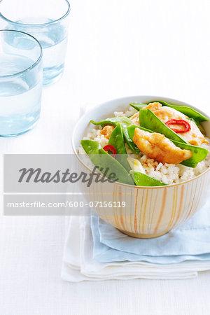 Chicken stir fry with rice in bowl, studio shot